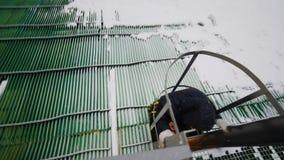 Ο εργαζόμενος ανυψώνει επάνω τη σκάλα μετάλλων στο έδαφος το χειμώνα απόθεμα βίντεο