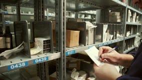 Ο εργαζόμενος αποθηκών εμπορευμάτων κάνει μια σημείωση στα έγγραφα και παίρνει έξω ένα κιβώτιο απόθεμα βίντεο