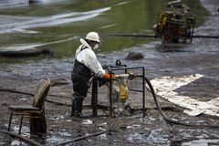 Ο εργαζόμενος αφαιρεί το αργό πετρέλαιο από μια παραλία Στοκ φωτογραφία με δικαίωμα ελεύθερης χρήσης
