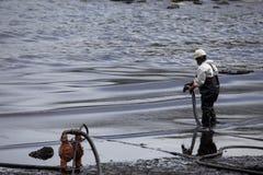 Ο εργαζόμενος αφαιρεί το αργό πετρέλαιο από μια παραλία Στοκ Φωτογραφίες