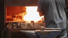 Ο εργαζόμενος βάζει τα γάντια και αναμιγνύοντας το ξύλο στο φούρνο που χρησιμοποιεί το πόκερ σφυρηλατήστε μέσα απόθεμα βίντεο