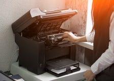 Ο εργαζόμενος γραφείων αλλάζει την κασέτα σε έναν εκτυπωτή λέιζερ στοκ εικόνες