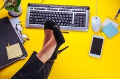 Ο εργαζόμενος γραφείων θηλυκών έχει μια γυναίκα υπολοίπου έβαλε τα πόδια της στον πίνακα Στοκ Εικόνα