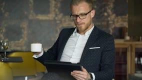 Ο εργαζόμενος γραφείων κάθεται στην καρέκλα, έγγραφα σχετικά με την ταμπλέτα στον καφέ απόθεμα βίντεο