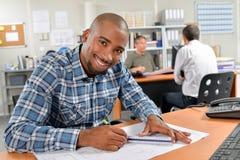 Ο εργαζόμενος γραφείων κάθισε το γράψιμο στο γραφείο Στοκ Εικόνα