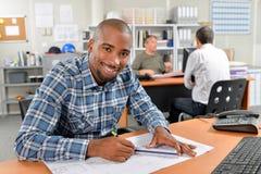 Ο εργαζόμενος γραφείων κάθισε το γράψιμο στο γραφείο Στοκ εικόνα με δικαίωμα ελεύθερης χρήσης