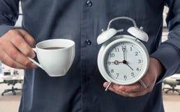 Ο εργαζόμενος γραφείων κρατά το φλιτζάνι του καφέ και το ξυπνητήρι Στοκ Φωτογραφία