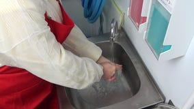 Ο εργαζόμενος γυναικών στην κόκκινη ποδιά πλένει τα χέρια της κάτω από τη βρύση απόθεμα βίντεο