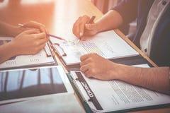 Ο εργαζόμενος δύο επιχειρήσεων συμβουλεύεται για το έγγραφο στοιχείων επιχείρησης στοκ εικόνα με δικαίωμα ελεύθερης χρήσης
