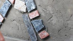 Ο εργαζόμενος εγκαθιστά την επιφάνεια τοίχων πετρών με το τσιμέντο απόθεμα βίντεο