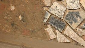 Ο εργαζόμενος εγκαθιστά την επιφάνεια τοίχων πετρών με το τσιμέντο φιλμ μικρού μήκους