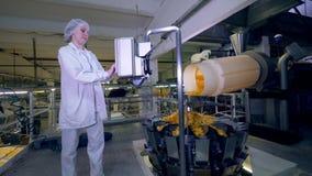 Ο εργαζόμενος εγκαταστάσεων χρησιμοποιεί μια μηχανή για να ελέγξει μια γραμμή με τα πατατάκια πατατών απόθεμα βίντεο