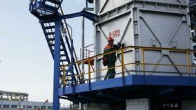 Ο εργαζόμενος ελέγχει τις συσκευές στην εναέρια άποψη πύργων παραγωγής απόθεμα βίντεο