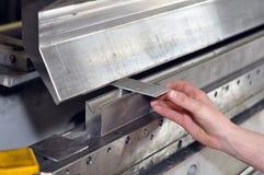 Ο εργαζόμενος ενεργοποιεί την κάμπτοντας μηχανή σε ένα κατασκευαστικό εταιρεία μετάλλων στοκ εικόνα
