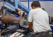 Ο εργαζόμενος ενεργοποιεί την οριζόντια πριονίζοντας μηχανή ζωνών στοκ εικόνες