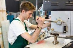 Ο εργαζόμενος ενεργοποιεί τη μηχανή διατρήσεων γυαλιού Στοκ Εικόνα