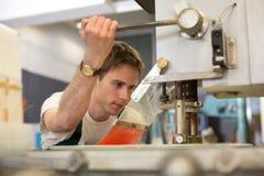 Ο εργαζόμενος ενεργοποιεί τη μηχανή διατρήσεων γυαλιού Στοκ εικόνες με δικαίωμα ελεύθερης χρήσης