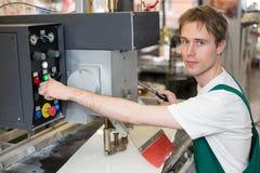 Ο εργαζόμενος ενεργοποιεί τη μηχανή διατρήσεων γυαλιού Στοκ Εικόνες