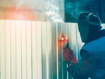 Ο εργαζόμενος ενώνει στενά το φράκτη μετάλλων υπαίθρια Στοκ εικόνες με δικαίωμα ελεύθερης χρήσης