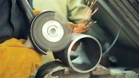 ο εργαζόμενος επεξεργάζεται το μέρος με μια αλέθοντας μηχανή απόθεμα βίντεο