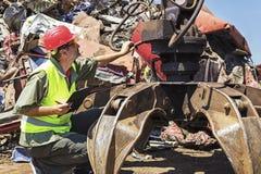 Ο εργαζόμενος επιθεωρεί το γερανό στο junkyard Στοκ εικόνα με δικαίωμα ελεύθερης χρήσης