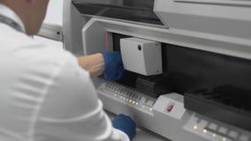 Ο εργαζόμενος εργαστηρίων εγκαθιστά τη μορφή με τους σωλήνες δοκιμής των ιατρικών δειγμάτων στη ιατρική συσκευή απόθεμα βίντεο