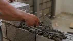 Ο εργαζόμενος εφαρμόζει το κονίαμα τσιμέντου σε έναν τοίχο για τις δομικές μονάδες, διανέμοντας ομοιόμορφα, χρησιμοποιώντας spatu απόθεμα βίντεο