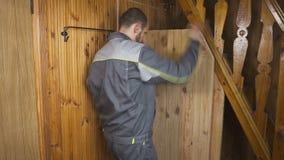Ο εργαζόμενος θέτει - επάνω μια μόνος-γίνοντη πόρτα σε ένα ξύλινο εσωτερικό φιλμ μικρού μήκους