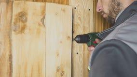 Ο εργαζόμενος θέτει - επάνω μια μόνος-γίνοντη πόρτα σε ένα ξύλινο εσωτερικό απόθεμα βίντεο