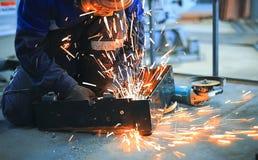 Ο εργαζόμενος κάθεται στο τσιμεντένιο πάτωμα στο εργαστήριο και το ενωμένο στενά μέρος μετάλλων Φωτεινοί σπινθήρες μυγών στοκ εικόνες με δικαίωμα ελεύθερης χρήσης