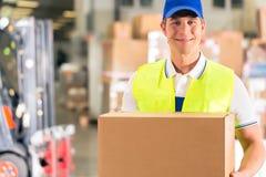 Ο εργαζόμενος κρατά τη συσκευασία στην αποθήκη εμπορευμάτων της διαβίβασης στοκ εικόνες