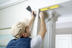Ο εργαζόμενος κρατά putty το μαχαίρι και μετρά τη γωνία τοίχων χρησιμοποιώντας τη γωνία μετάλλων Στοκ εικόνες με δικαίωμα ελεύθερης χρήσης