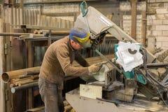 Ο εργαζόμενος κυβερνήτης μετρά ένα κομμάτι προς κατεργασία μετάλλων για την κοπή σε ένα πριόνι ζωνών Στοκ φωτογραφία με δικαίωμα ελεύθερης χρήσης