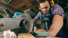 Ο εργαζόμενος κόβει το ξύλο, χρησιμοποιώντας το κυκλικό πριόνι σε ένα εργαστήριο απόθεμα βίντεο