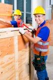 Ο εργαζόμενος κλείνει ένα ξύλινο κιβώτιο με το σφυρί και το καρφί Στοκ φωτογραφίες με δικαίωμα ελεύθερης χρήσης
