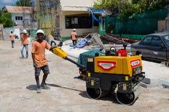 Ο εργαζόμενος μεταγλωττίζει το έδαφος χρησιμοποιώντας τη μηχανή Στοκ Φωτογραφία
