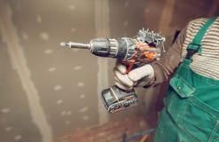 Ο εργαζόμενος με τα προστατευτικά γάντια είναι holdind ένα τρυπάνι στο διαμέρισμα που είναι κάτω από την κατασκευή, αναδιαμόρφωση στοκ εικόνα
