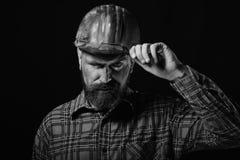 Ο εργαζόμενος με τη βάναυση εικόνα φορά το βρώμικο κόκκινο κράνος και το ελέγχει Οικοδόμος ή ανθρακωρύχος με την παχιά γενειάδα Κ Στοκ Εικόνα