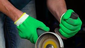 Ο εργαζόμενος με τη γωνιακή αλέθοντας μηχανή κόβει το μέταλλο φιλμ μικρού μήκους