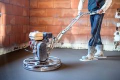 Ο εργαζόμενος με τη δύναμη trowel σχεδιάζει το τσιμεντένιο πάτωμα λήξης, ομαλή συγκεκριμένη επιφάνεια στην κατασκευή σπιτιών Στοκ φωτογραφία με δικαίωμα ελεύθερης χρήσης
