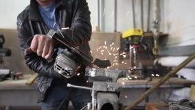 Ο εργαζόμενος με το μύλο γωνίας κάνει τη μεταλλουργία στο βιομηχανικό περιβάλλον φιλμ μικρού μήκους