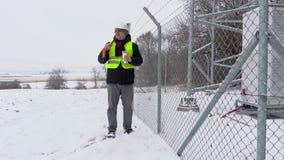 Ο εργαζόμενος με το φτυάρι χιονιού που περπατούν κοντά στο φράκτη και η έναρξη πίνουν το τσάι απόθεμα βίντεο