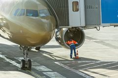 Ο εργαζόμενος μηχανικών μηχανικών ελέγχει τον ανεμιστήρα μηχανών του αεροπλάνου πριν από την αναχώρηση από τον αερολιμένα Στοκ Φωτογραφία