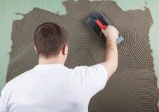 Ο εργαζόμενος οικοδόμος εφαρμόζει την κόλλα σε έναν τοίχο για ένα κεραμικό κεραμίδι φ Στοκ φωτογραφία με δικαίωμα ελεύθερης χρήσης
