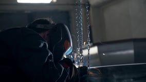 Ο εργαζόμενος οξυγονοκολλητών στις φόρμες και σε μια μάσκα συγκόλλησης ενώνει στενά την ανοξείδωτη μεγάλη σκάφη ή τη λίμνη λουτρώ φιλμ μικρού μήκους