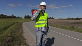 Ο εργαζόμενος οδοποιίας με τον κώνο κυκλοφορίας στον ώμο παρουσιάζει ο Κ χειρονομία φιλμ μικρού μήκους