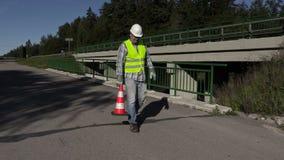 Ο εργαζόμενος οδοποιίας παρουσιάζει χειρονομία στάσεων και έβαλε τον κώνο κυκλοφορίας φιλμ μικρού μήκους