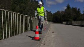 Ο εργαζόμενος οδοποιίας συλλέγει τα οδικά σημάδια φιλμ μικρού μήκους
