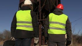 Ο εργαζόμενος παίρνει τις οδηγίες από το μηχανικό κοντά στις δεξαμενές μετάλλων απόθεμα βίντεο