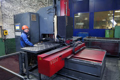 Ο εργαζόμενος παρακολουθεί την εργασία της μηχανής για τα πιάτα χάλυβα με τρυπάνι Στοκ Εικόνες